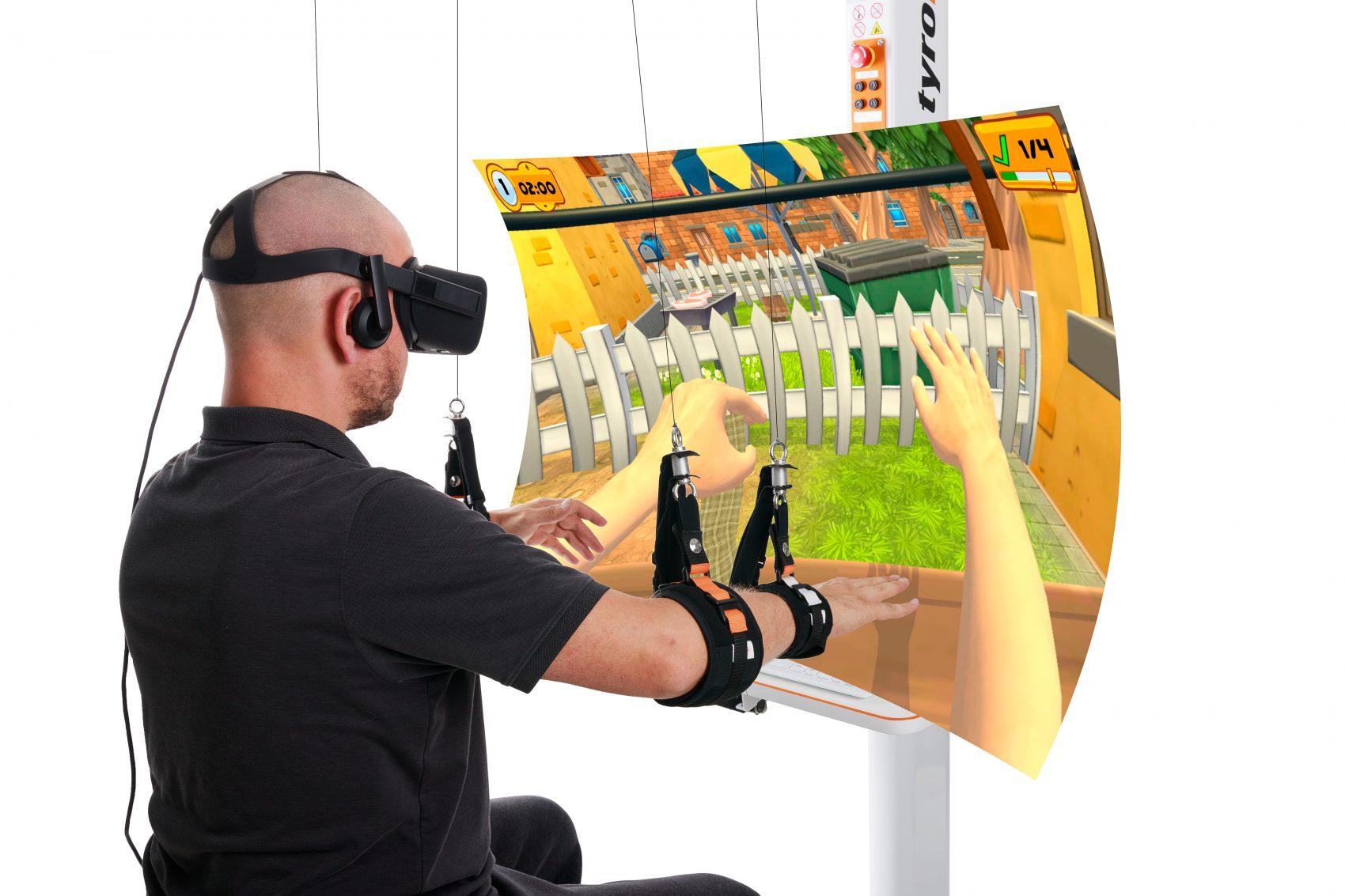 DIEGO in Anwendung, Patient hat virtuelle Brille auf, beide Arme in den Armschlingen und sitzt vorm Bildschirm